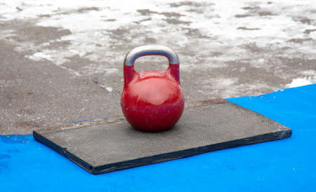 A large red kettlebell on the gym floor. Banco de Imagens - 167322323