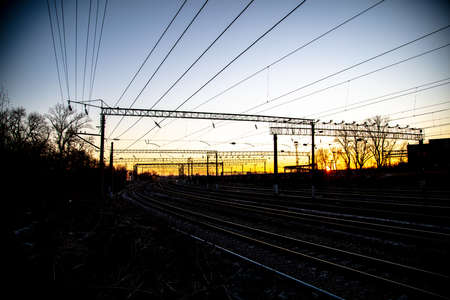Poles with electric wires near the railway at sunset. Banco de Imagens - 167320887