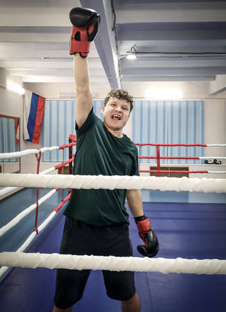 A male boxer rejoices over the victory in the ring.