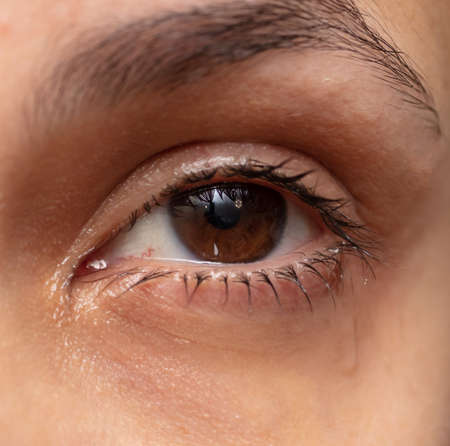 Eyes with tears of a crying girl. Close-up