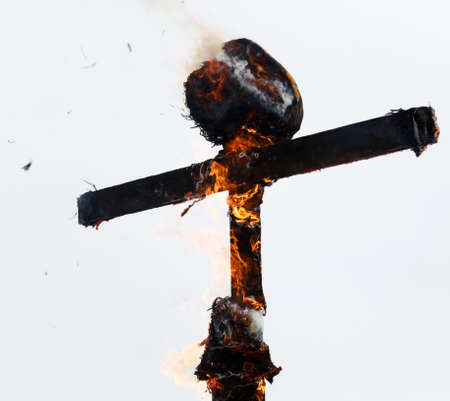 A wooden cross is burning with fire against a gray sky.