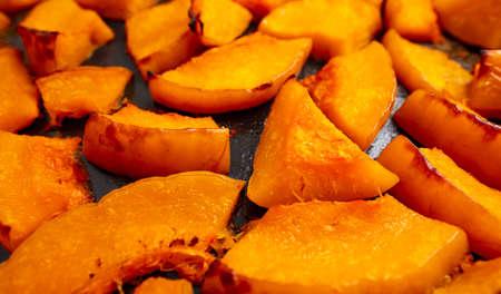 Pieces of pumpkin baked on a baking sheet.