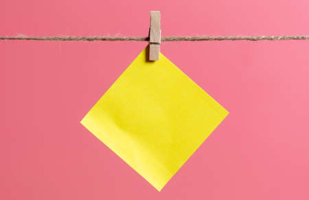 A yellow piece of paper hanging on a rope on a pink background.