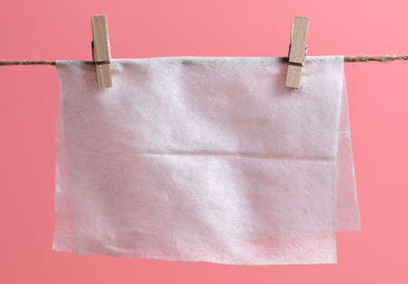 White paper hanging on a rope on a pink background.
