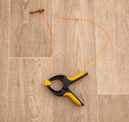 Construction clothespin on a wooden parquet. Banco de Imagens