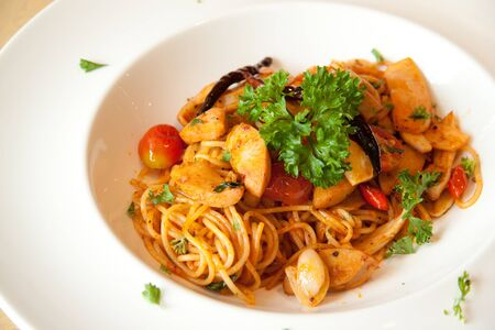 Freshly cooked plate of spaghetti with saucesage sprinkled with fresh green herbs.