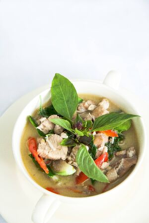 Green curry with pork and basil in with bowl on white background photo