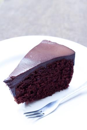 trozo de pastel: Pastel de chocolate en un plato blanco y el folk Foto de archivo