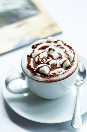 Hot chocolate with marshmallow on white table photo