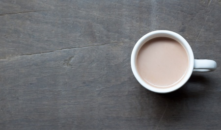 A white cup of hot cocoa on wood background