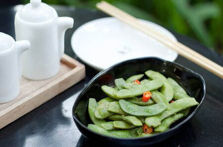 green beans with red chilli in black ceramic bowl photo