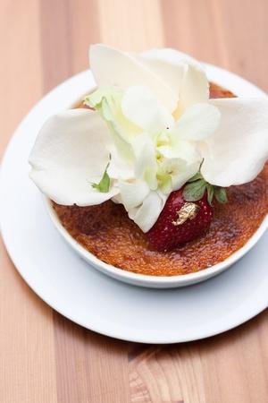 creme brul�e decorar con p�talos de color blanco en el plato blanco