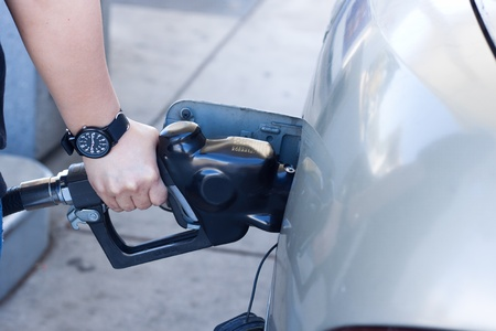 close up of woman hand putting gas into the car at gas station photo