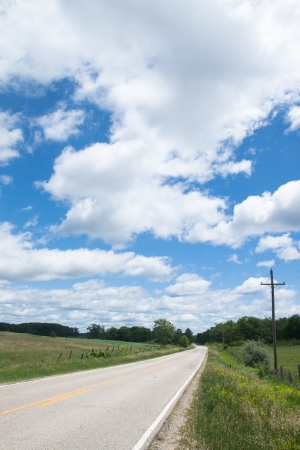 Country road in a cloudy day and blue sky photo