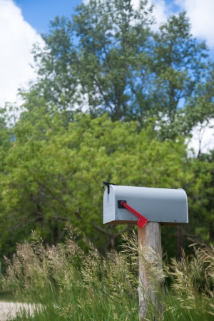 Rural mailbox on an old wooden stand on the country road photo