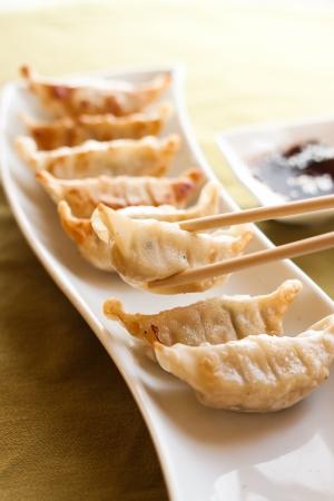 Gyoza and chopsticks on white plate photo