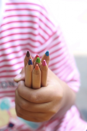 A child hold color pencils with a little hand photo
