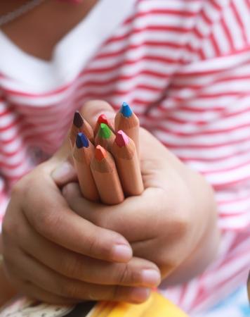 Un ni�o l�pices de colores de retenci�n con una peque�a mano