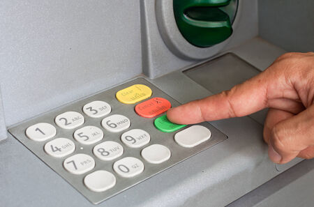Close-up of hand entering PINpass code on ATMbank machine keypad photo