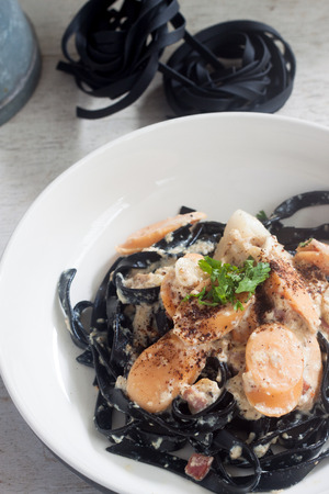 Carbonara squid ink with sausages on white plate Stock Photo