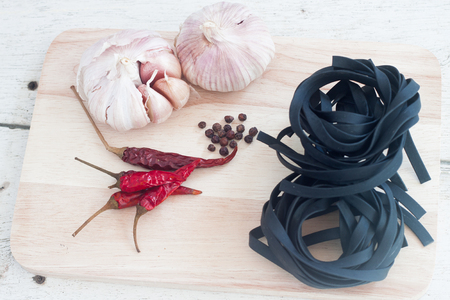 Squid ink black tinted twirl of a tagliatelle on table wood Stock Photo