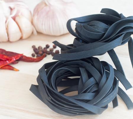 La tinta del calamar giro tintado negro de un tagliatelle sobre madera mesa