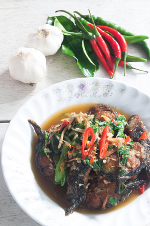 Thai Food Spicy Cat Fish with vegetable on desk (Pla Duk Pad Ped)
