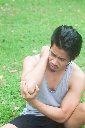 自然の中でアジア人の肘の痛み草背景