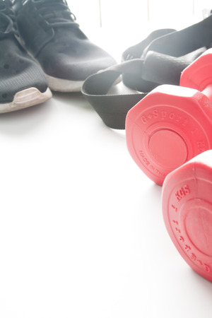 Red dumbbells and sport wear in fittness background. Sport wear, Sport fashion, Sport accessories, Sport equipment. Stock Photo