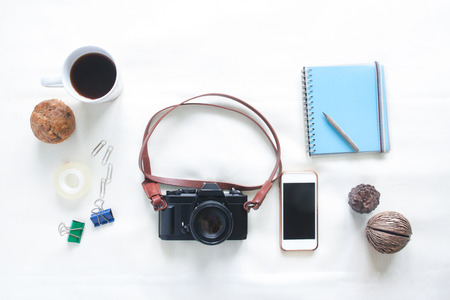 Top view of working elements with film camera, smartphone and a cup of coffee on white background