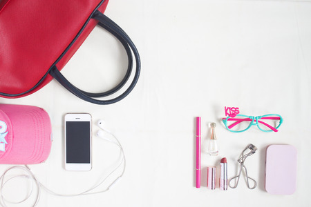 Overhead view of essential beauty items, Top view of smartphone, red hand bag, fashion eyeglasses and cosmetic Stock Photo