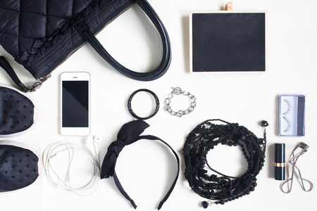 Woman Accessories, cosmetics, shoulder bag, note pad and smartphone in black concept, top view, flat lay Stock Photo