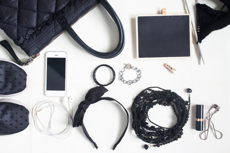 leatherette: Woman Accessories, cosmetics, shoulder bag, note pad and smartphone in black concept, top view, flat lay Stock Photo
