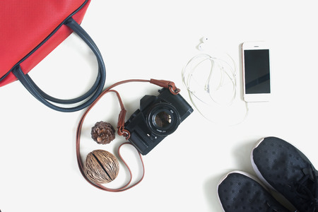 Flat lay of travel items with film camera, smartphone, red hand bag and sneaker