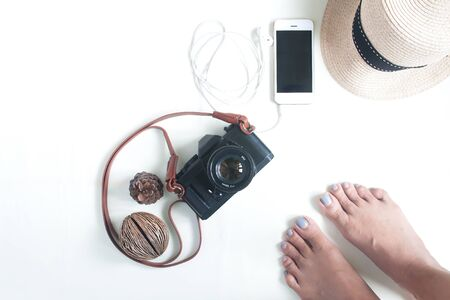 Selfie of barefoot with travel items, film camera, smartphone and accessories on white background, flat lay, top view