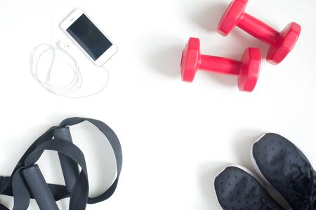 Sport fitness items with smartphone on white background, flat lay, top view, copy space