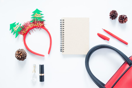 cosmetics bag: Christmas composition. Christmas fashion for girl, cosmetics, bag, pine cones, notebook and red pen with copy space. Flat lay, top view Stock Photo