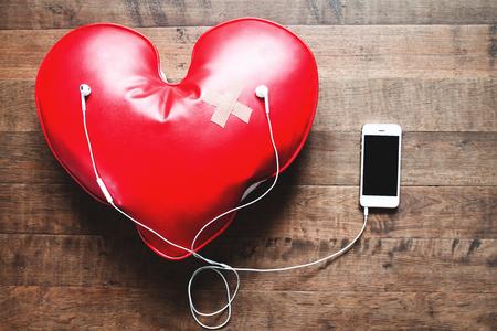 빨간색 붕대로 듣는 음악 휴대 전화에서 음악을 듣고, 나무 바닥에 깨진 심장 개념