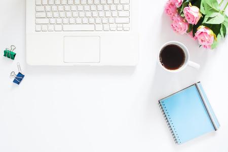 Draufsicht auf Computer Laptop, eine Tasse Kaffee, rosa Rosen und Notebook auf weißem Hintergrund, Copy space Standard-Bild
