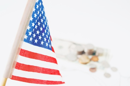 USA flag, stack of coins and dollors in background, selective focus. Travel America concept