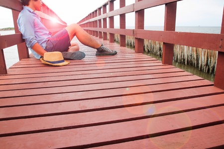 A man in casual clothing sitting alone on wooden bridge, Broken heart concept Stock Photo