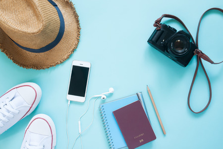 Flat lay of travel items with mobile device, passport and camera on pastel color background