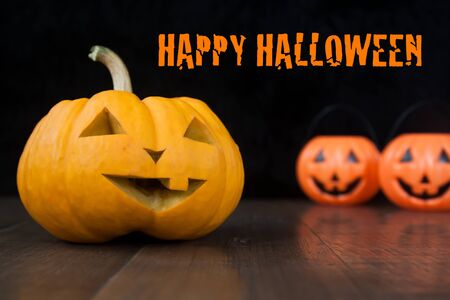 Halloween still life with pumpkins on wooden floor and dark background with Happy halloween text Stock Photo