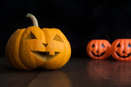 Halloween still life with pumpkins on wooden floor and dark background
