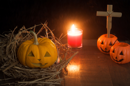 Halloween still life with pumpkins and candle on wooden floor and dark background