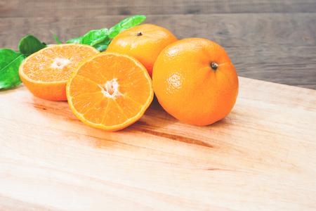 Fresh oranges on wooden table in kitchen