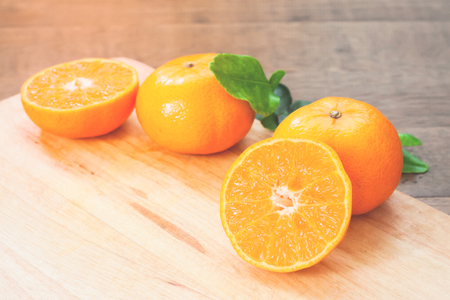 Fresh oranges on wooden table in kitchen with sunlight