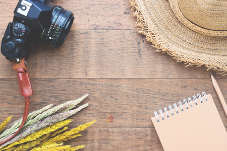Creative flat lay of Autumn concept with dried flowers, camera, straw hat and notebook on wood background