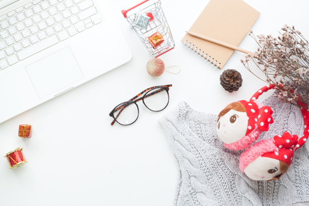 Top view of Christmas and winter shopping online concept on white desk. White laptop, shopping cart, gift boxes, notebook, eyeglasses and woman accessories