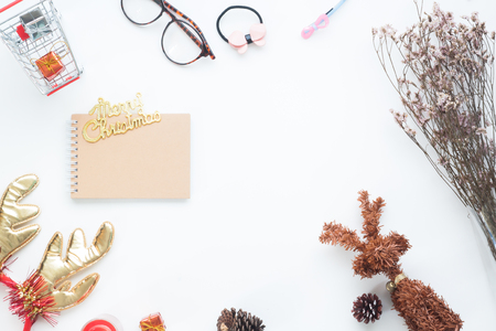 Creative flat lay of Christmas decorations and notebook on white background with copy space